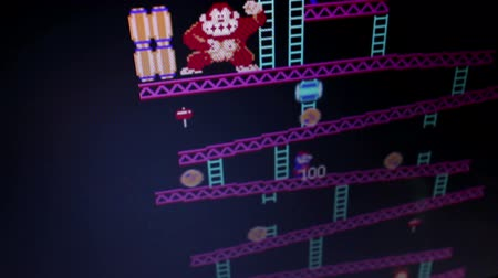 caracteres : HIgh angle wide shot Donkey Kong retro arcade vintage videogame during game play, as seen from player POV; camera dolly to follow some action 2  Released in 1981, Donkey Kong was an important milestone in the videogame industry.