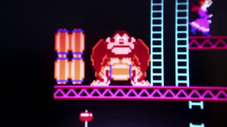 villain : Close up of Donkey Kong with primary gorilla antogonist rolling barrels to thwart his foes; camera dollies to follow some action.  Released in 1981, Donkey Kong was an important milestone in the videogame industry. Stock Footage