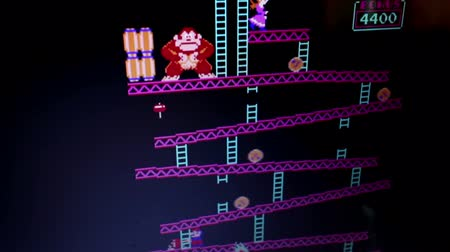 caracteres : Wide shot Donkey Kong retro arcade vintage videogame during game play from playr POV. Camera dollies to follow some action. Released in 1981, Donkey Kong was an important milestone in the videogame industry. Stock Footage