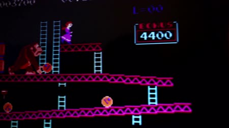 arcada : Medium shot of Donkey Kong classic videogame main screen, with camera dolly to follow some action. Shot with special lenses not a screen capture during a motion game play analysis. Released in 1981, Donkey Kong was an important milestone in the videog