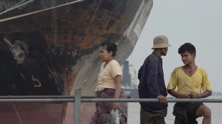 porters : PORT, QUAY  JETTY:  ASIA - Porters carry sacks along a gangway with cargo ships visible behind;