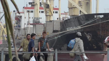 porters : Porters carry sacks along a gangway past two bystanders, with large cargo ship visible in background;