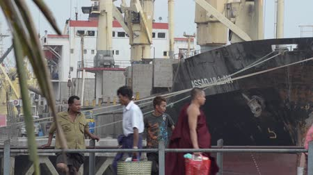 работник физического труда : PORT, QUAY  JETTY:  ASIA - Worker carries a large sack past bystanders standing in front of a large ship; Стоковые видеозаписи