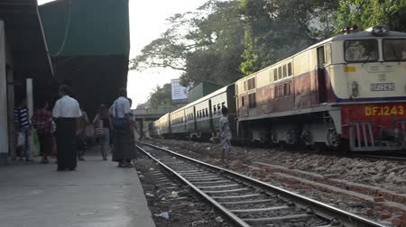 áruk : TRAIN LOCOMOTIVE: Wide shot of sunny train arriving on far platform. From  Diesel Train in Myanmar  Asia , one of many clips from this series from StockFootageWorld