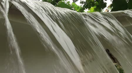 pacífico : Low angle  close up of a small manmade waterfall in tropical Southeast Asia; palm trees and other Asian trees and vegetation can be seen in back.