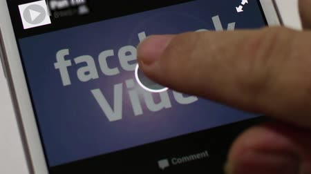 Close up of a smartphone screen with conceptual-illustrative video showing Facebook Video. User presses play button and screen clip plays with built in flare before dolly away.  Facebook continues to gain ground against Youtube in the video space, makin Стоковые видеозаписи