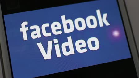 phablet : Extreme close up of smartphone video player featuring illustrative video clip, Facebook Video; video plays then concludes, with camera dolly away and return afterwards. Facebook continues to gain ground against Youtube in the video space, making this il
