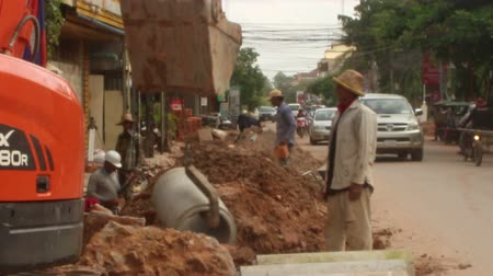 ROADSIDE CONSTRUCTION: An excavator digs a trench near passing traffic on the roadside in Southeast Asia Stock Footage