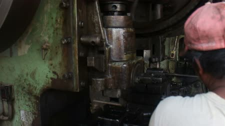 Medium close up of large metal stamping press in operation, as seen over the shoulder of worker, at vintage old-school metalworking machine shop in the developing world. Stock Footage