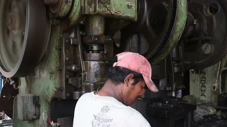 Medium shot of large metal stamping machine with huge metal turning wheels and gears at vintage old-school metalworking machine shop in the developing world, a worker stands in foreground, tending the machine. Stock Footage