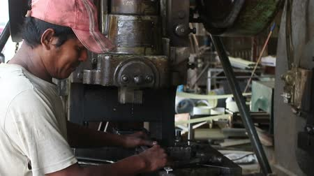 Medium close up of worker placing metal blanks into position in a large metal stamping machine at vintage old-school metalworking machine shop in the developing world. Stock Footage