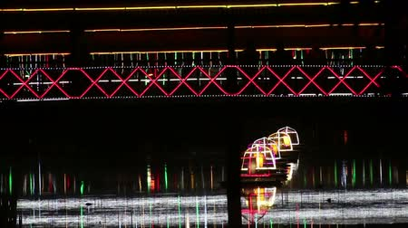 Medium shot of pedestrians seen in silhouette crossing an illuminated footbridge at night in Asia. A row of glowing buoys drift on a small river below. Стоковые видеозаписи