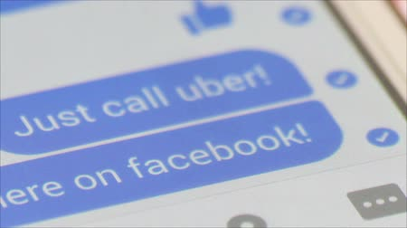 navrhnout : Call Uber - Macro close up of a smartphone chat window with a chat text saying just call uber!, the ride hailing service which is aligned with Facebook services.  a funger of the user can be partly seen.