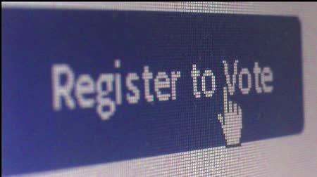 választotta : Macro close up of  a large blue online banner saying Register to Vote; user moves hand cursor and clicks on it. Shot at pixel level with special lenses. (*not a screengrab). One of a series of macro election and voting clips by StockFootageWorld.