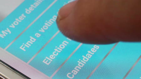 phablet : Macro close up of  a user tapping an online voting app to find Election results on a smartphonetablet screen, shot at pixel level. (*not a screengrab). One of a series of macro election and voting clips by StockFootageWorld.
