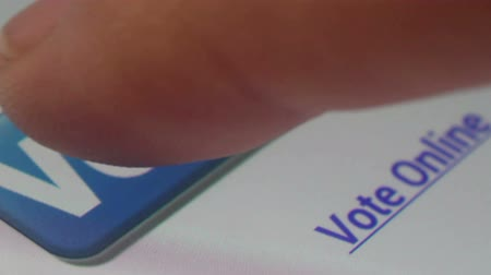 választotta : Ultra macro close up of a user scrolling through an online voting app on a tablet or smartphone, then tapping a button which reads Vote Now, shot at pixel level with special lenses. (*not a screengrab). Stock mozgókép