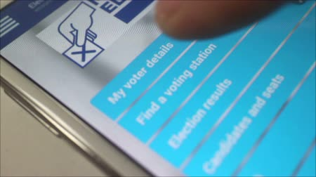 phablet : Macro close up of user pressing an online voting button on a smartphone or tablet, online voting and voter registration is becoming more common. Shot at pixel level. (*not a screengrab).