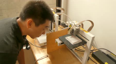 készítő : Medium CU of Asian youth inspecting a 3D printer in operation in a maker space lab. Shot cuts to continuation of the action