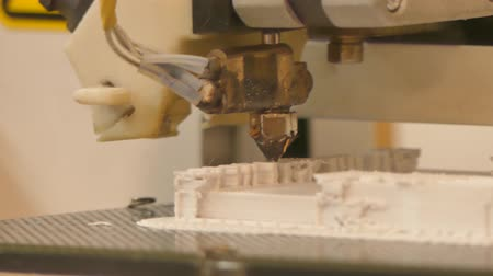 Extreme close up of a 3D printer in operation with a white object in a tray, working in a maker-space coworking lab. One of a series by StockFootageWorld Stock Footage