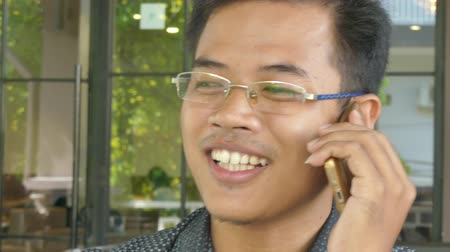 przywództwo : Close up of a young Asian male professional chatting with a colleague on his smartphone. Shot then pulls out and reframes to a medium close up  One of a series of multicultural business and lifestyle clips