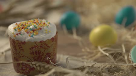 motivo : putting eggs on Easter table with Easter selebration cake panettone also called kulich glazed with icing, raisins and Sprinkles