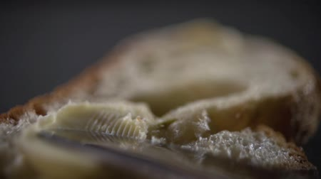 migalha : The butter is slowly smeared onto the bread.