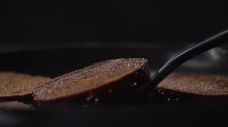 кухонная посуда : A close-up of a toasted piece of bread turns over and falls into the pan.