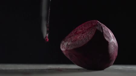 purificado : A sharp blade cuts the beet into pieces.