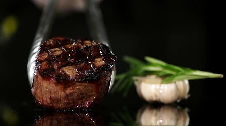 lombo de vaca : Grilled steak is placed on a dark surface.