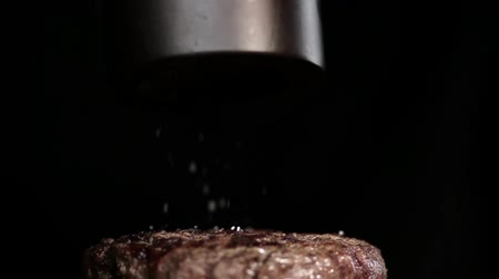 lombo de vaca : Sprinkled salt falls on the surface of the steak.