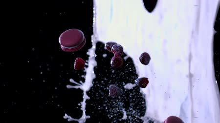 Macaroon and berries fly through the flow of milk.