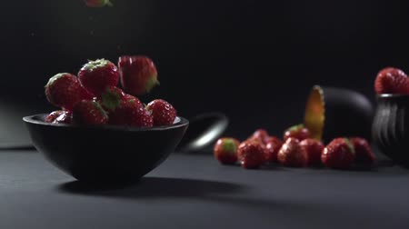 backround : Strawberries fall into a bowl with berries.