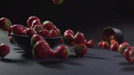 Strawberries are collected in a bowl and scattered to the surface.