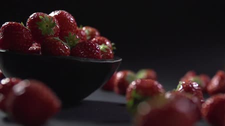 foods : Strawberry rolls down from a stone bowl to the surface.
