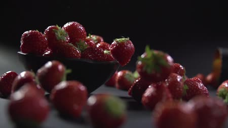 black raspberry : Strawberry falls on a bunch of berries in a bowl and rolls to the surface. Stock Footage