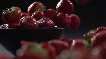 Strawberries fall out of the bowl on the surface.