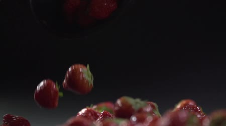 A bowl with strawberries is tipped and the berries are falling.