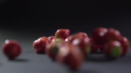 backround : Two bowls are turned over and the berries fall out of them.