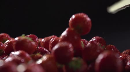 backround : Berries fall on a layer of fresh strawberries.