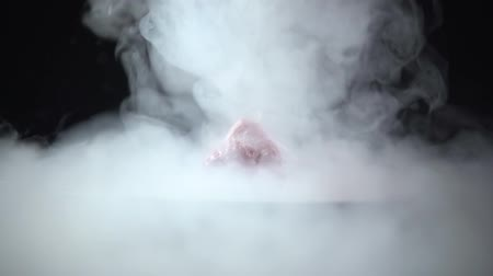 Drops and smoke of liquid nitrogen poured onto the top of the strawberry. Stok Video
