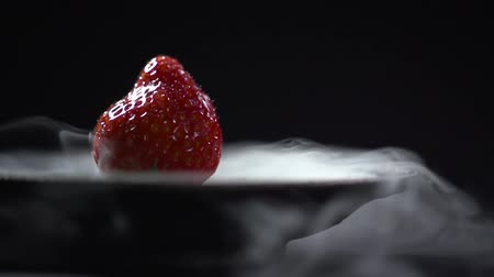 backround : Close-up of a strawberry in the smoke of dry ice on a plate.