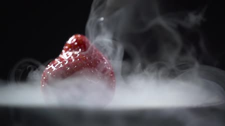 A stream of liquid pours over the berry from above and the smoke dissipates.