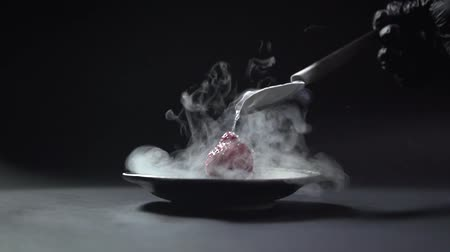 A spoon with liquid nitrogen drops to the strawberry.