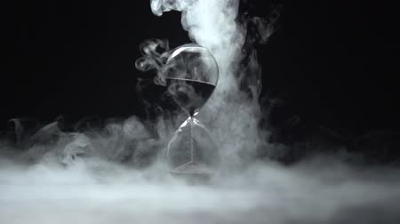 visszaszámlálás : The smoke dissipates around the hourglass with dark sand. Stock mozgókép