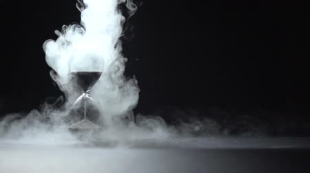 Smoke of liquid nitrogen pours on the glass hourglass in the frame.