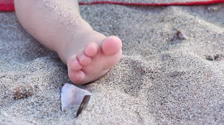 kumlu : Detail of a child playing in the sand on the beach among shells, with her tiny toes.