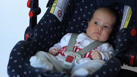 necessity : Little baby is sitting protected on a baby car seat.