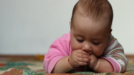 salya : Little baby is playing with her fingers as she is having fun trying to calm the pain of gums due to teething. Stok Video