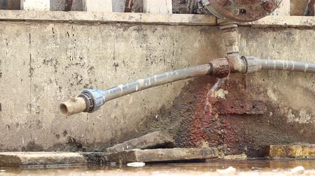 paslanmış : A rusty water pipe fitting leaks forming a puddle of fresh water. A fitting is used in pipe plumbing systems to connect straight pipe or tubing sections, to adapt to different sizes or shapes, and for other purposes, such as regulating or measuring fluid  Stok Video