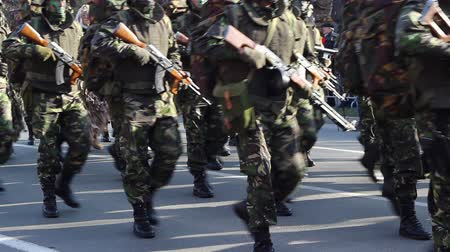 bulletproof : Soldiers with guns to chest, in camouflage uniform, with painted face, are marching.